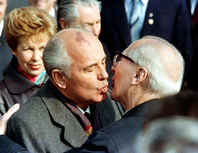 Soviet Leader Mikhail Gorbachev and his wife, Raisa, are welcomed by East German Leader Erich Honecker (R) with a fraternal kiss in East Berlin after the Gorbachev's arrive to celebrate the 40th anniversary of East Berlin, October 6, 1989. (Photo by Reuters/Stringer)