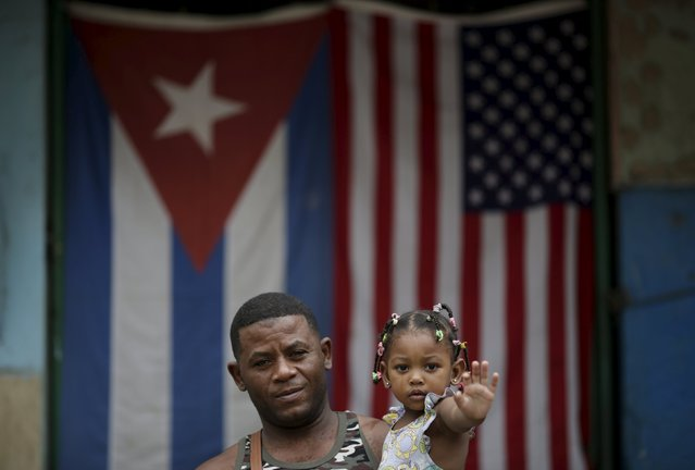 "Yoendry Gainsa, 35, a bricklayer, holds his daughter while posing for a photograph in front of the Cuban and U.S. flags in Havana, March 25, 2016. Regarding Obama's historic visit to the island, Gainsa said ""I hope everything gets better and that there will be better work and development for our children. Long live Obama"". (Photo by Ueslei Marcelino/Reuters)"