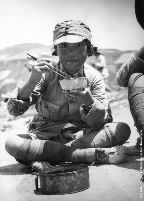 1935: A Chinese university student in military uniform sits cross-legged on the ground as she enjoys a simple meal during the war between China and Japan