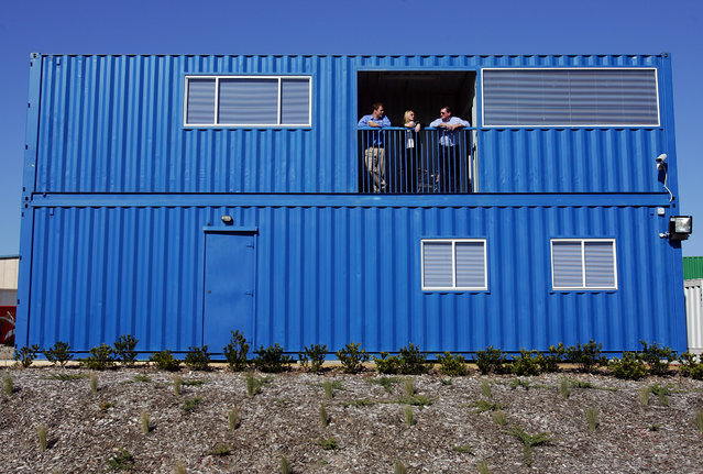 Potential buyers stand with an agent on the balcony of a three-bedroom home made from four old shipping containers in Sydney August 1, 2005. The two-storey mobile home includes two bathrooms, timber floors, air conditioning, a kitchen, laundry, balcony and sewage treatment tank, which can be pulled apart in less than a day for ease of transportation. (Photo by David Gray/Reuters)