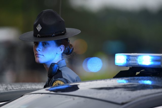 """A Virginia State Trooper guards a roadblock on June 1, 2019, at the scene of the mass shooting in the Virginia Beach Municipal center in Virginia, Beach, Virginia. A municipal employee sprayed gunfire """"indiscriminately"""" in the government building complex on May 31, 2019, police said, killing 12 people and wounding four in the latest mass shooting to rock the US. (Photo by Eric Baradat/AFP Photo)"""