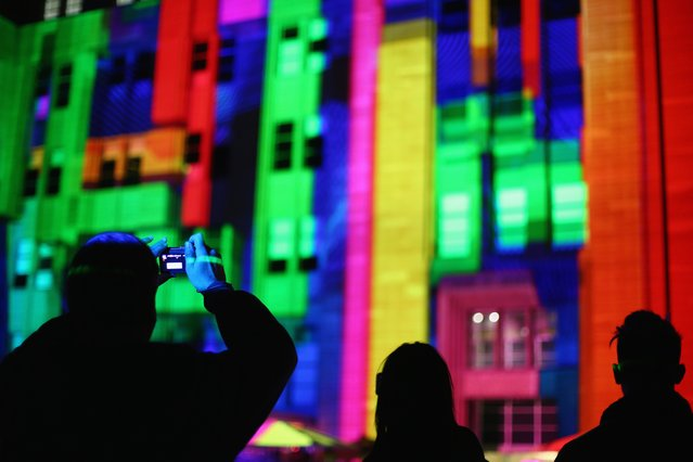 "Festival visitors watch the ""Mechanised Colour Assemblage"" installation illuminated on the Museum of Contemporary Art Australia façade as part of the Vivid Sydney Festival on May 24, 2015 in Sydney, Australia. Vivid Sydney is an annual festival that features light sculptures and installations throughout the city. The festival takes place May 22 through June 8. (Photo by Mark Kolbe/Getty Images)"