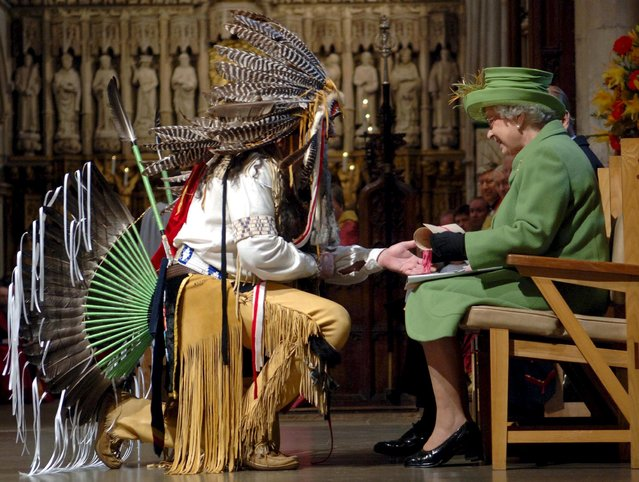 Britain's Queen Elizabeth (R) receives a scroll from Bruce Two Dogs Bozsum at Southwark Cathedral in London, in this November 22, 2006 file. (Photo by Stefan Rousseau/Reuters)