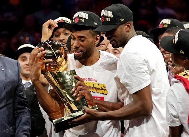 Toronto Raptors forward Kawhi Leonard (2) and Toronto Raptors center Serge Ibaka (9) celebrate with the Larry O'Brien Trophy after the Golden State Warriors in game six of the 2019 NBA Finals at Oracle Arena in Oakland, CA, USA on June 13, 2019. (Photo by Kyle Terada/USA TODAY Sports)