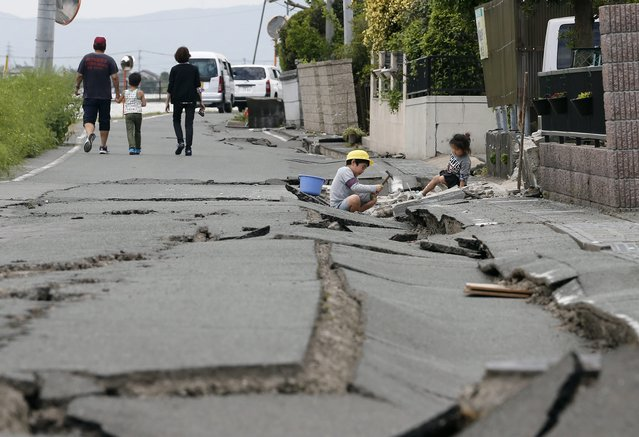 A boy and his younger sister play amid cracks in a road in front of their house following a second powerful earthquake, in Mashiki, Kumamoto Prefecture, southwestern Japan, 16 April 2016. A 7.3 magnitude earthquake that struck southwestern Japan early 16 April has now left 19 dead and a thousand injured, in a region where a day before another powerful quake claimed ten lives. The latest quake occurred on Kyushu island's western coastal prefecture of Kumamoto, with an epicenter located about 10 kilometers deep. (Photo by Kimimasa Mayama/EPA)