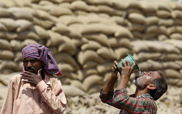 A labourer drinks water as another looks on, on a hot summer day at a grain market in Chandigarh, India April 19, 2016. (Photo by Ajay Verma/Reuters)
