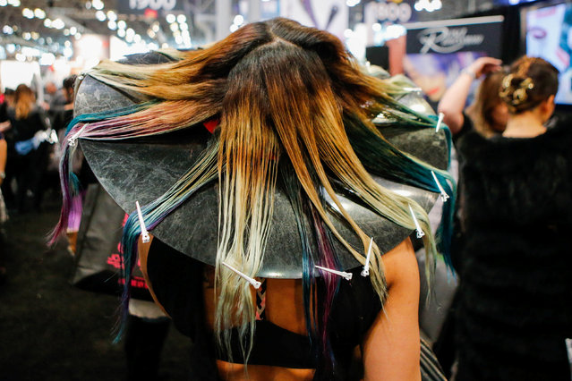 A woman has her hair done as people visit the International Beauty Show New York at Javits Center in New York, U.S., March 13, 2017. (Photo by Eduardo Munoz/Reuters)
