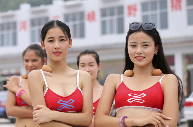 Contestants of a tourism beauty pageant balance eggs on their collarbones as they cruise along the Yellow River in Jiyuan, Henan province, China, June 22, 2015. The contestants believe that if they are slim enough, their collarbones will allow them to balance the eggs securely on their bodies. (Photo by Reuters/Stringer)