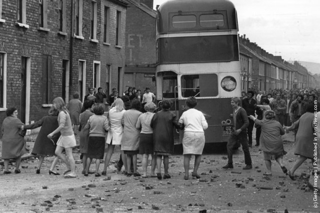 1970:  A commandeered bus is driven backwards through a picket of women who want the violence to end during riots on the Falls Road, Belfast