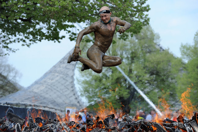 "A participant of the ""Spartan Race"" jumps over a fire at the Olympiapark in Munich, southern Germany, Saturday, April 12, 2014. The participants had to overcome numerous obstacles on the route through the race. (Photo by Andreas Gebert/AP Photo/DPA)"