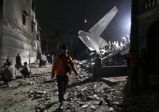 Rescuers search for victims at the site where an Indonesian air force cargo plane crashed in Medan, North Sumatra, Indonesia, Tuesday, June 30, 2015. (Photo by Binsar Bakkara/AP Photo)