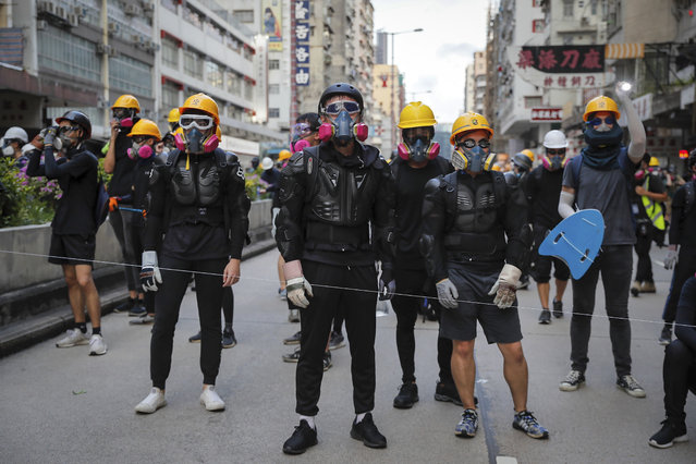 Protesters with protection gears face with riot policemen on a street during the anti-extradition bill protest in Hong Kong, Sunday, August 11, 2019. (Photo by Kin Cheung/AP Photo)
