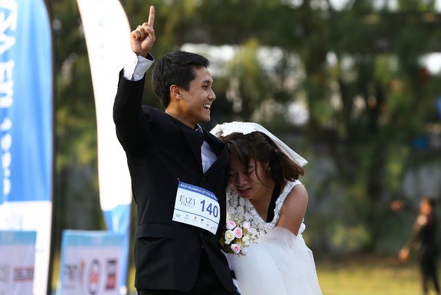 """Rittchai Prasonsin, 27, and Sirada Thamwanna, 29, react after winning the """"Running of the Brides"""" race in a park in Bangkok, Thailand March 25, 2017. (Photo by Athit Perawongmetha/Reuters)"""