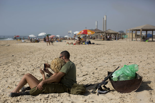 In this Saturday, June 27, 2015 photo, Israeli soldiers enjoy the day on the beach next to kibbutz Zikim, on the Israel-Gaza border. (Photo by Oded Balilty/AP Photo)