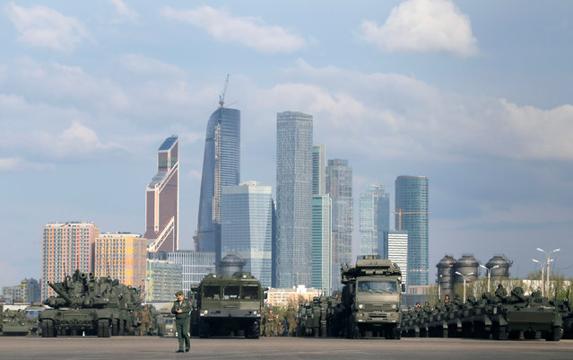 """Russian military vehicle columns are seen at a range before a rehearsal for the Victory Day parade, with the Moscow International Business Center also known as """"Moskva-City"""" seen in the background, in Moscow, Russia, May 5, 2016. (Photo by Maxim Shemetov/Reuters)"""