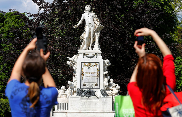 Two women take photographs of the Wolfgang Amadeus Mozart monument in Vienna, Austria, May 6, 2016. (Photo by Heinz-Peter Bader/Reuters)