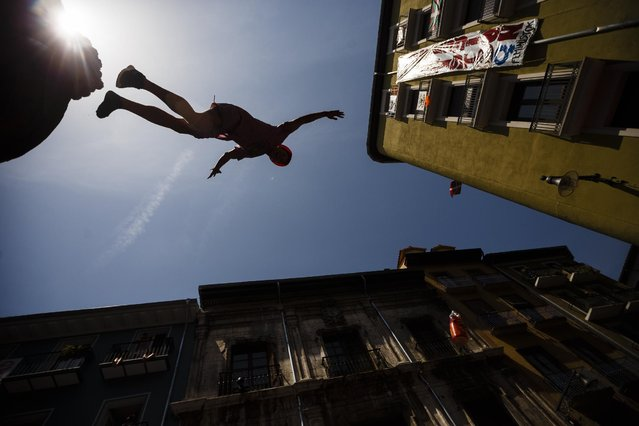 """A reveler jumps towards his friends as they celebrate during the launch of the """"Chupinazo"""" rocket, to celebrate the official opening of the 2015 San Fermin fiestas in Pamplona, Spain, Monday, July 6, 2015. (Photo by Daniel Ochoa de Olza/AP Photo)"""