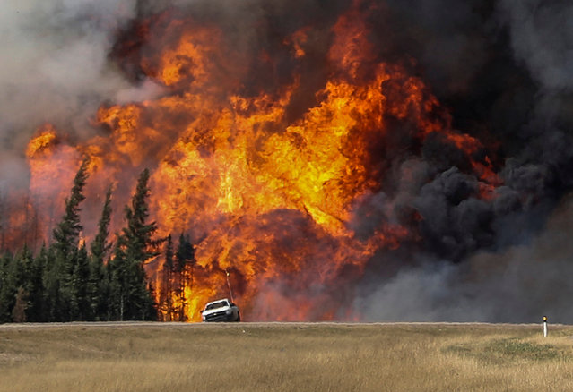 Smoke and flames from the wildfires erupt behind a car on the highway near Fort McMurray, Alberta, Canada, May 7, 2016. (Photo by Mark Blinch/Reuters)