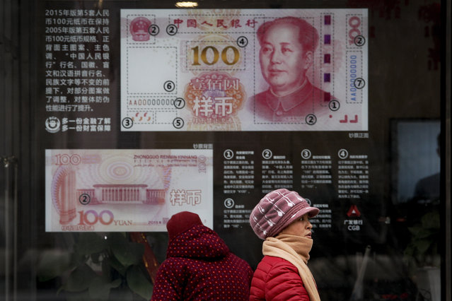 In a Monday, February 18, 2019 file photo, women walk by a bank window panel displaying the security markers on the latest 100 Yuan notes in Beijing. The Trump administration has again decided not to label China or any other country as a currency manipulator. But in a report to Congress, the administration is keeping China on a list of countries whose trade surpluses with the United States and other indicators are closely tracked.  (Photo by Andy Wong/AP Photo/File)