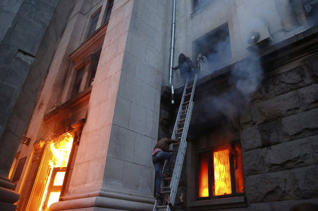 People wait to be rescued on the second storey's ledge during a fire at the trade union building in Odessa May 2, 2014. (Photo by Yevgeny Volokin/Reuters)