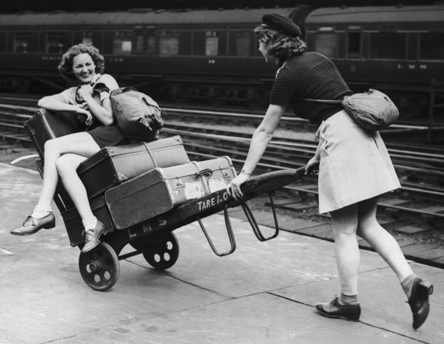 Two holidaymakers amuse themselves with a porter's trolley whilst waiting for their train at Euston Station, London, 5th August 1939. (Photo by A. J. O'Brien/Fox Photos/Getty Images)