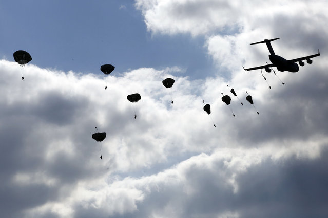 """Troops from the U.S. Army's 173rd Infantry Brigade Combat Team parachute from a Boeing C-17 Globemaster III during a NATO-led exercise """"Orzel Alert"""" held together with Canada's 3rd Battalion and Princess Patricia's Light Infantry, and Poland's 6th Airborne Brigade in Bledowska Desert in Chechlo, near Olkusz, south Poland May 5, 2014. The training includes parachuting, airborne operations and infantry skills. (Photo by Kacper Pempel/Reuters)"""