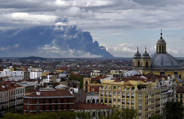 Picture taken from the Almudena cathedral in Madrid shows a huge smoke column caused by a fire in an uncontrolled dump near the town of Sesena, on May 13, 2016. A huge waste ground near Madrid where millions of tyres have been dumped was on fire today, releasing a thick black cloud of toxic fumes that officials worry could harm residents nearby. (Photo by Gerard Julien/AFP Photo)