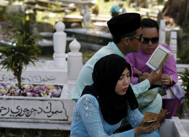 A family recite prayers at relatives graves on Eid Al-Fitr in Kuala Lumpur, Malaysia, July 17, 2015. (Photo by Olivia Harris/Reuters)