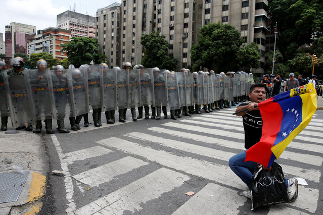 An opposition supporter carrying a Venezuelan flag kneels in front of National Guards during a rally to demand a referendum to remove President Nicolas Maduro in Caracas, Venezuela, May 18, 2016. (Photo by Carlos Garcia Rawlins/Reuters)