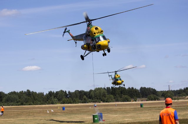 Pilots on the helicopters MI-2 compete during an Air Sports Festival on the outskirts of Minsk, Belarus, July 18, 2015. (Photo by Vasily Fedosenko/Reuters)