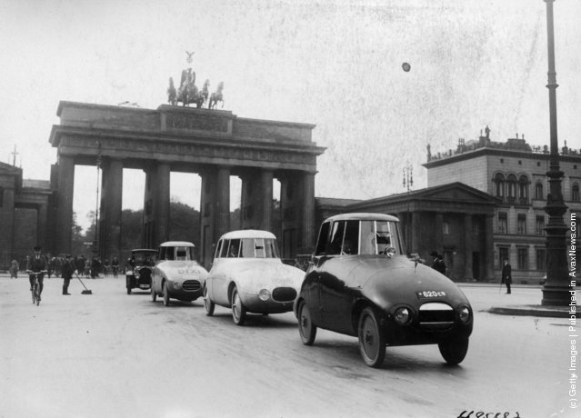 A pioneering experimental streamlined car with bodywork designed by Hungarian-born German aerodynamicist Paul Jaray being driven around the streets of Berlin for the first time, circa 1935. The Brandenburg Gate is in the background