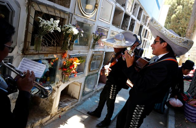 Mariachi musicians play as people attend the Day of the Dead at the central cemetery in La Paz, Bolivia, early morning, November 2, 2019. (Photo by Kai Pfaffenbach/Reuters)