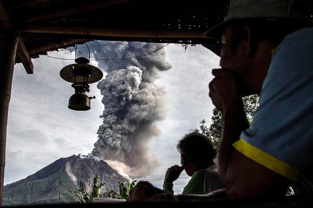 Villagers look on as Mount Sinabung volcano spews thick volcanic ash, as seen from Beganding village in Karo, North Sumatra province, on May 19, 2017. Sinabung roared back to life in 2010 for the first time in 400 years. After another period of inactivity, it erupted once more in 2013 and has remained highly active since. (Photo by Ivan Damanik/AFP Photo)