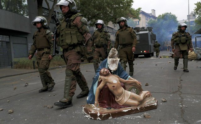 Police advance on anti-government protesters, past a religious statue that protesters removed from a church and then damaged, in Santiago, Chile, Friday, November 8, 2019. Chile's president on Thursday announced measures to increase security and toughen sanctions for vandalism following three weeks of protests that have left at least 20 dead. (Photo by Esteban Felix/AP Photo)