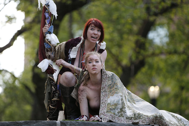 "Gina Marie Russell, left, as the sorcerer ""Prospero"",and Marisa Roper as ""Miranda"", headline an all-female cast who at times perform fully nude during the Outdoor Co-ed Topless Pulp Fiction Appreciation Society Theater Company's production of Shakespeare's ""The Tempest"", in Central Park, Thursday, May 19, 2016, in New York. This production of ""Tempest"" focuses on the contrast between the harsh restrictions of ""civilization"" and the Edenic, magic-suffused tropical island on which the sorcerer Prospero and his daughter Miranda live in exile for twelve years. The play, which will also be performed Friday afternoon, was staged at Summit Rock, Central Park's highest elevation. (Photo by Kathy Willens/AP Photo)"