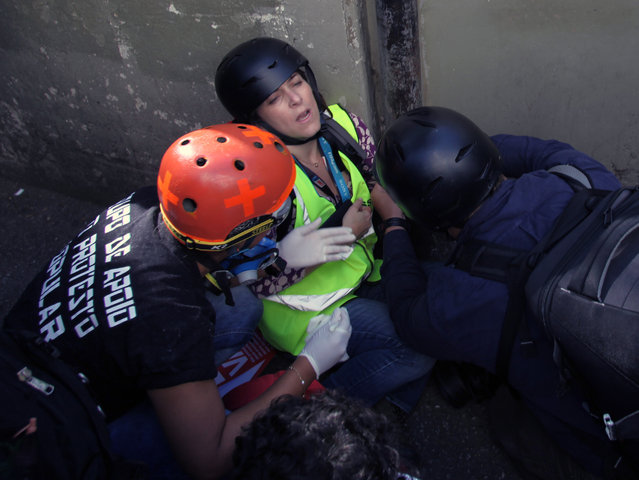 A journalist working for CNN is assisted after being injured in clashes between demostrators and mlitary police during a protest against the 2014 World Cup, in Sao Paulo June 12, 2014. (Photo by Reuters)