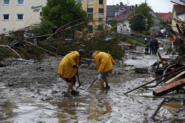People clear the street from flood damages in the Bavarian village of Simbach am Inn east of Munich, Germany, June 1, 2016. (Photo by Michaela Rehle/Reuters)