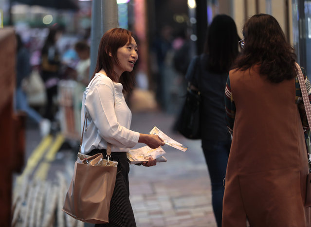 In this photo taken Thursday, November 7, 2019, district council candidate Cathy Yau distributes flyers to pedestrians during her campaign at Causeway Bay in Hong Kong. Yau, a former police officer, grew exasperated as police used more force to quell the unrest. She quit the force in July after 11 years and is running in Sunday's district polls that are widely expected to deliver a decisive victory for the six-month-old movement seeking democratic reforms in the semi-autonomous Chinese territory. (Photo by Dita Alangkara/AP Photo)
