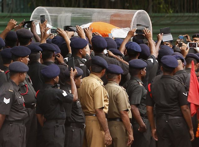 Indian soldiers use their mobile phones to take pictures of the body of former Indian President A. P. J. Abdul Kalam, wrapped with the national flag, outside Kalam's residence in New Delhi, India, July 28, 2015. (Photo by Anindito Mukherjee/Reuters)
