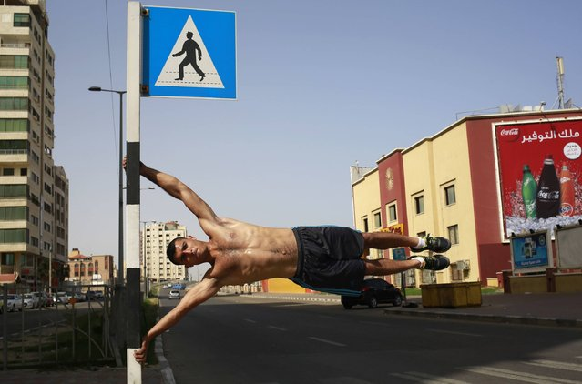 Baker Magadma, a member of Palestinian sports group Bar Palestine, performs on the street in Gaza City, on June 3, 2016. Street workout, which is still new in Gaza, is a growing sport across the world with annual competitions and events. (Photo by Mohammed Abed/AFP Photo)