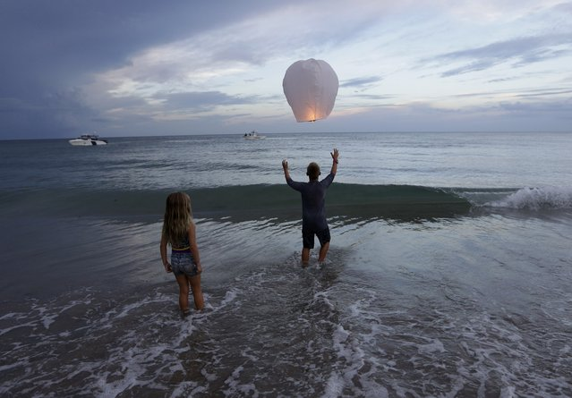 Andrew Grubowski, 10, of Palm City, Fla., releases a lantern during a vigil for Austin Stephanos and Perry Cohen, Tuesday, July 28, 2015, in Stuart, Fla. The two teenagers have been missing since last Friday when they went out on a boat to go fishing from Tequesta, Fla. A search continues for the boys from the Atlantic waters off Daytona Beach, Fla, north through Savannah, Ga. (Photo by Lynne Sladky/AP Photo)