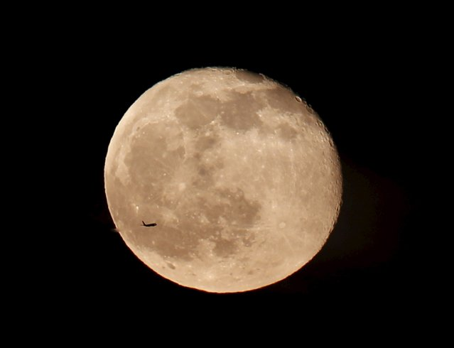 A silhouetted airplane flies past a full moon over Istanbul, Turkey May 5, 2015. (Photo by Osman Orsal/Reuters)