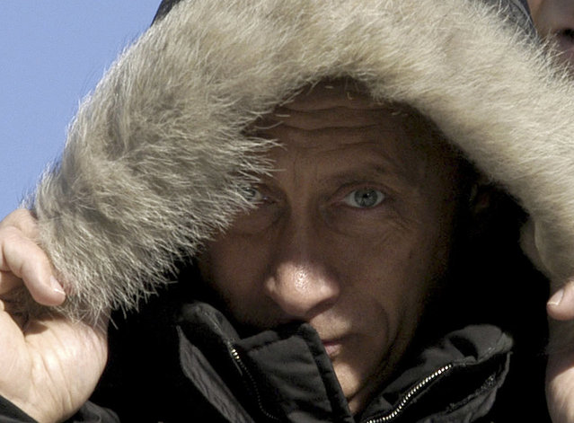 Russian President Vladimir Putin covers his head in a cold wind at the village of Ovsyanka near Krasnoyarsk, some 3,400 km ( 2,100 miles ) east of Moscow, where he continued his pre-election trip, Friday, February 27, 2004. Russians will vote at presidential elections on March 14, 2004. (Photo by AP Photo/ ITAR-TASS/Presidential Press Service)