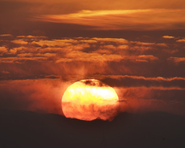 The sun rises between clouds in Frankfurt, Germany, early Wednesday, March 27, 2019. (Photo by Michael Probst/AP Photo)