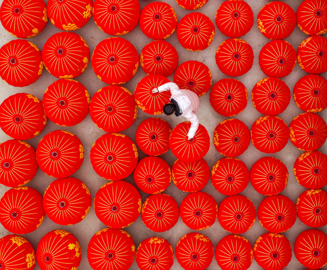 A worker at a factory making red lanterns in Sihong County, Jiangsu Province, China on December 23, 2019. (Photo by Costfoto/Barcroft Media)