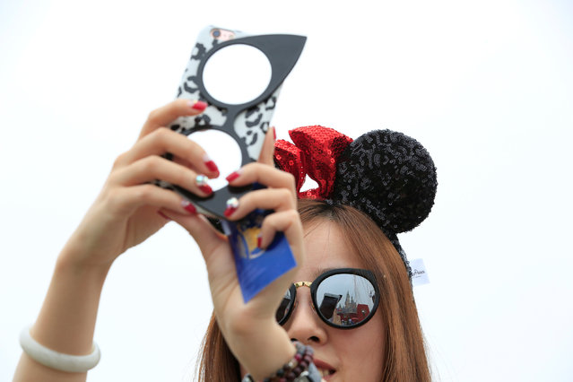 A girl takes pictures after opening ceremony at Shanghai Disney Resort in Shanghai, China, June 16, 2016. (Photo by Aly Song/Reuters)
