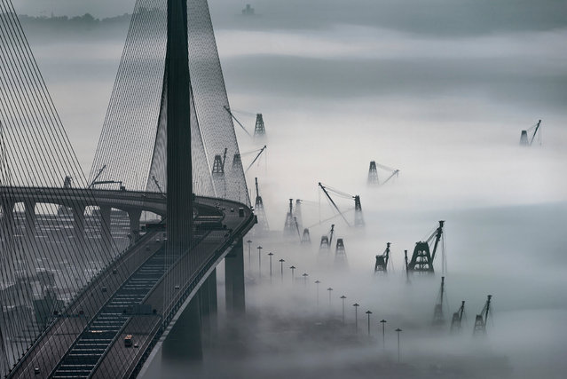 """Fog and mist in Hong Kong. """"When warm winds bring the promise of spring from the southern ocean, sea fog anchors around Hong Kong's harbours. This photo captured the stunning view of the fog at the Kwai Chung Container Terminal. Only the cranes of the container ships and the twin towers of the Stonecutters Bridge are visible through the swirling mist"""". (Photo by Edward Tin/NatGeo Cities Travel Photographer of the Year 2017)"""