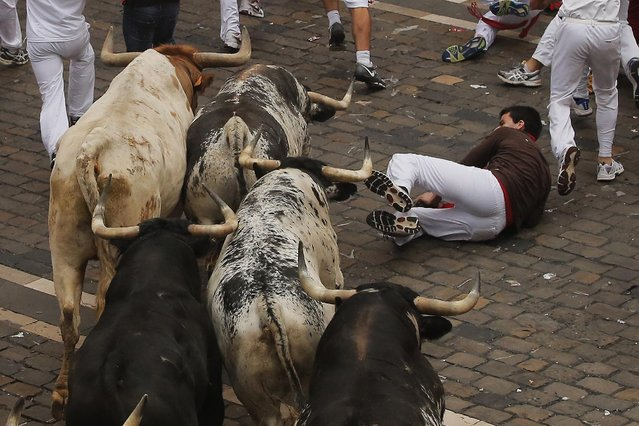 A reveler falls as a Torrestrella fighting bulls run during the running of the bulls of the San Fermin festival, in Pamplona, Spain, Monday, July 7, 2014. (Photo by Andres Kudacki/AP Photo)