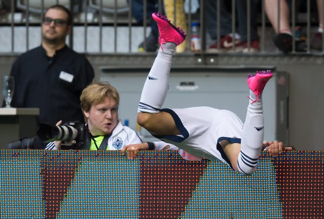 Vancouver Whitecaps' Pedro Morales, of Chile, tumbles over the advertising boards after colliding with Seattle Sounders' Micheal Azira during the first half of a CONCACAF Champions League soccer game Wednesday, August 5, 2015, in Vancouver, British Columbia. (Photo by Darryl Dyck/The Canadian Press via AP Photo)