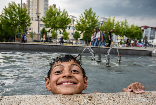 Children of the Roma community play as they cool off in a fountain in the main square of Pristina, Kosovo on June 14, 2017. (Photo by Armend Nimani/AFP Photo)